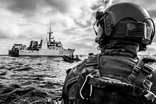 A Royal Canadian Navy member from HMCS EDMONTON and United States Coast Guard (USCG) Law Enforcement Detachment (LEDET) members practice vessel tactical approaches as they test their communication with HMCS Edmonton during Operation CARIBBE, 25 October 2018.